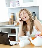 Delighted woman using a phone and laptop in the kitchen