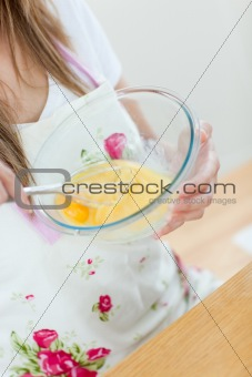 Close-up of a teen woman preparing a cake in the kitchen