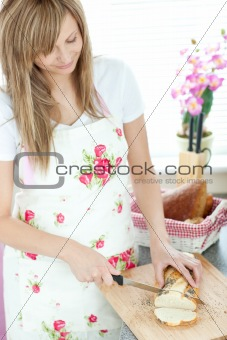 Attractive woman cutting bread in the kitchen