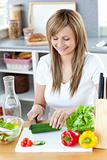 Delighted woman preparing a healthy meal in the kitchen