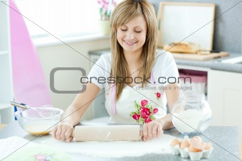 Portrait of an attractive woman preparing a cake in the kitchen