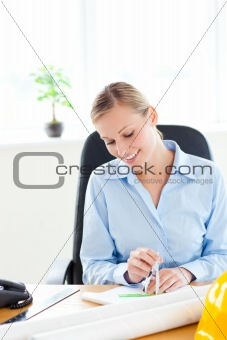 Attractive female architect studying a project