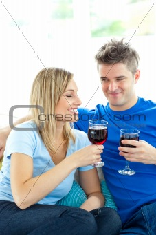 Adorable couple drinking wine together in the living-room