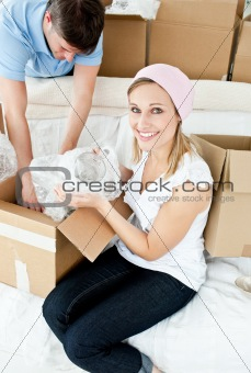 Cheerful couple unpacking boxes after moving