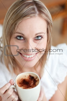 Bright woman drinking a coffee sitting on a sofa