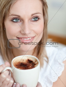 Beautiful woman drinking a coffee sitting on a sofa