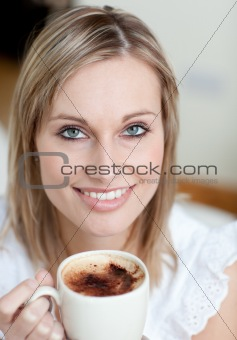 Charming woman drinking a coffee sitting on a sofa