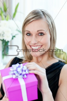Glowing woman opening a gift sitting on a sofa