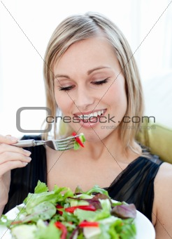 Portrait of a charming woman eating a salad