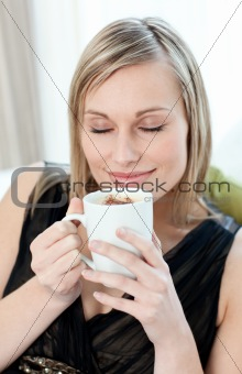 Relaxed woman drinking a coffee sitting on a sofa