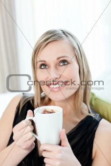 Radiant woman drinking a coffee sitting on a sofa