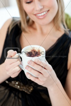 Blond woman drinking a coffee sitting on a sofa