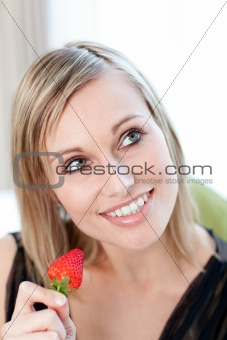 Bright woman eating a strawberry
