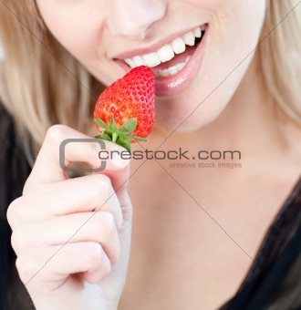 Caucasian woman eating a strawberry
