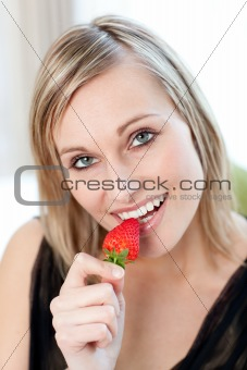 Radiant woman eating a strawberry
