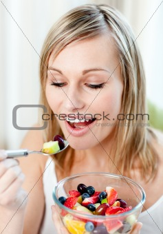 Beautiful woman eating a fruit salad
