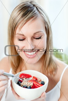 Bright woman eating muesli with fruits