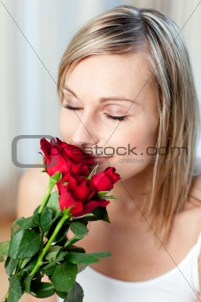 Beautiful woman smelling roses