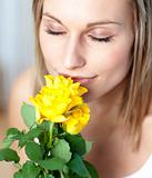 Attractive woman smelling roses