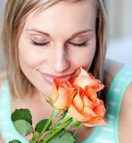 Smiling woman smelling roses