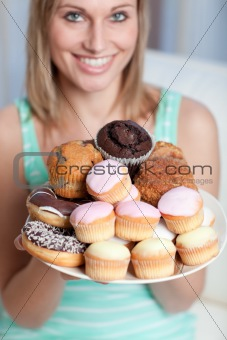 Blond woman holding a plate of cakes at home