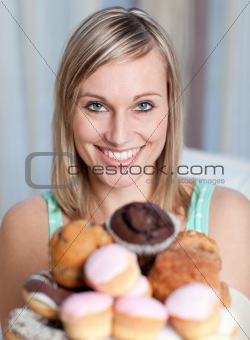 Bright woman holding a plate of cakes