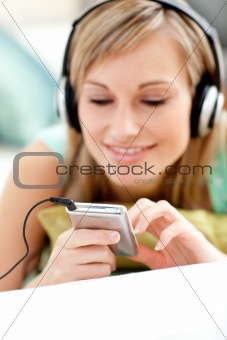 Attractive blond woman listening music lying on a sofa