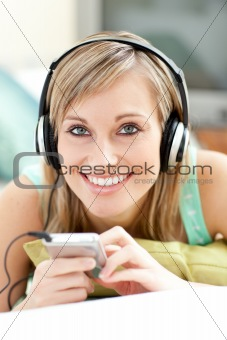 Charming young woman listening music lying on a sofa