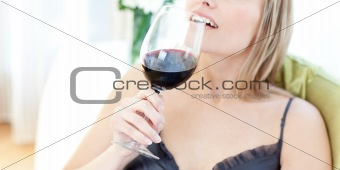 Beautiful blond woman drining red wine sitting on a sofa