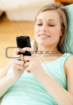 Bright young woman sending a text lying on a sofa