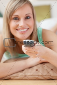 Smiling blond woman watching TV lying on the floor
