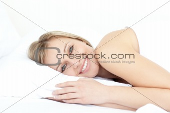 Bright woman relaxing on her bed