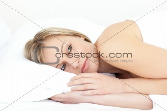 Bright young woman relaxing on her bed