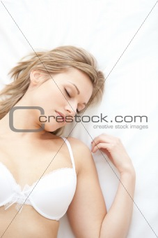 Asleep woman in underwear lying on bed