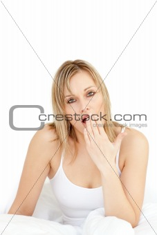 Charming woman yawning on her bed