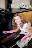 Smiling woman cleaning the oven