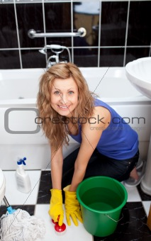 Positive young woman cleaning bathroom's floor