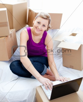 Cute woman using a laptop in the living-room