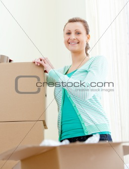 Attractive woman writing on boxes using a pen