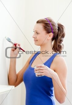 Beautiful woman is decorating a room