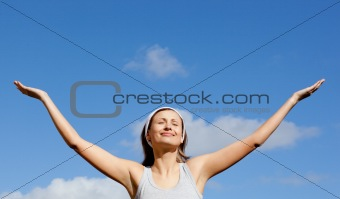 Glowing woman relaxing against blue sky