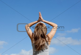Blond woman meditating against a blue sky