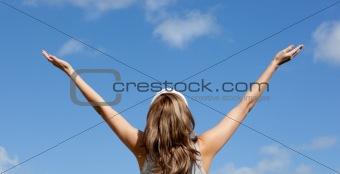 Caucasian blond woman punching tha air against blue sky