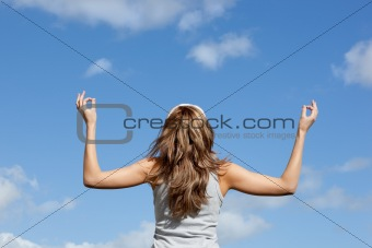 Caucasian woman meditating against a blue sky
