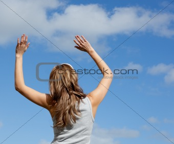 Caucasian woman doing yoga against a blue sky