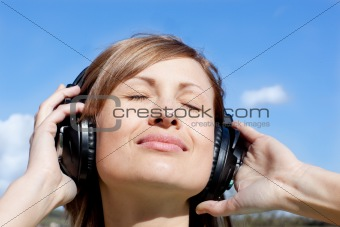 Beautiful woman listenng music outdoors