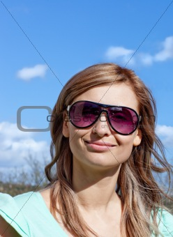 Smiling blond woman with sunglasses outdoors