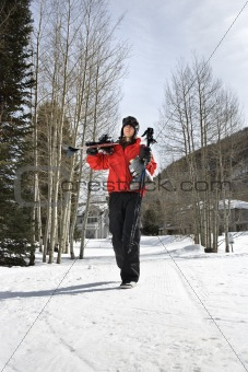 Teenager carrying ski gear.