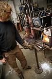 Metalsmith heating metal in forge.