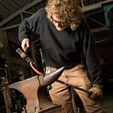 Metalsmith shaping metal.